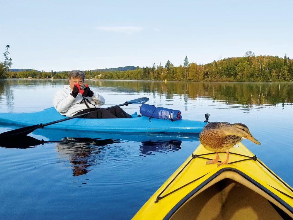 A fellow kayaker (in blue kayak) capturing a shot of the mallard perches on Mark's kayak