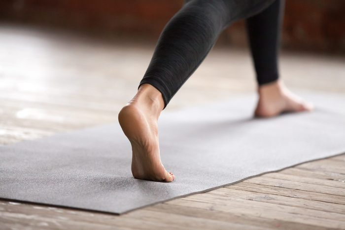 Young sporty woman practicing yoga, doing Warrior one exercise, Virabhadrasana 1 pose, working out, wearing black sportswear, indoor, yoga studio close up. Healthy lifestyle concept