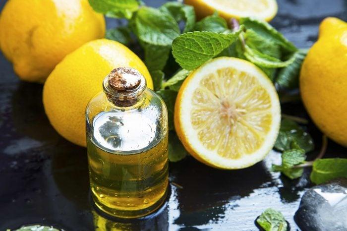 Lemon essential oil bottle with lemon fruits and mint leaves