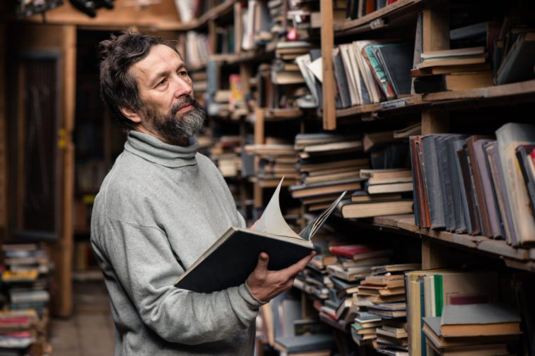 Portrait of authentic senior man with beard and good eyes reading book in the hand on bookshelf background
