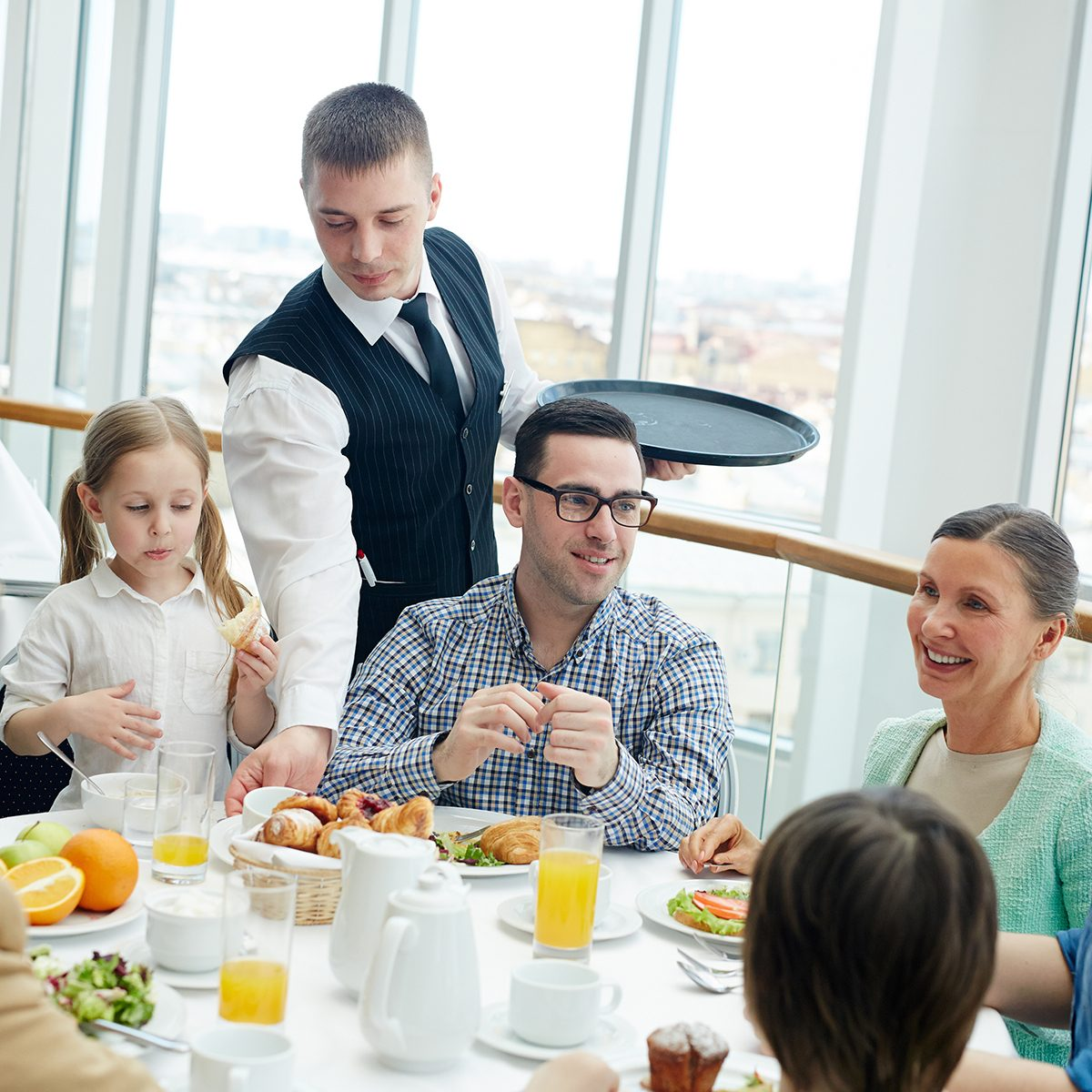 Young waiter serving big family during dinner or breakfast