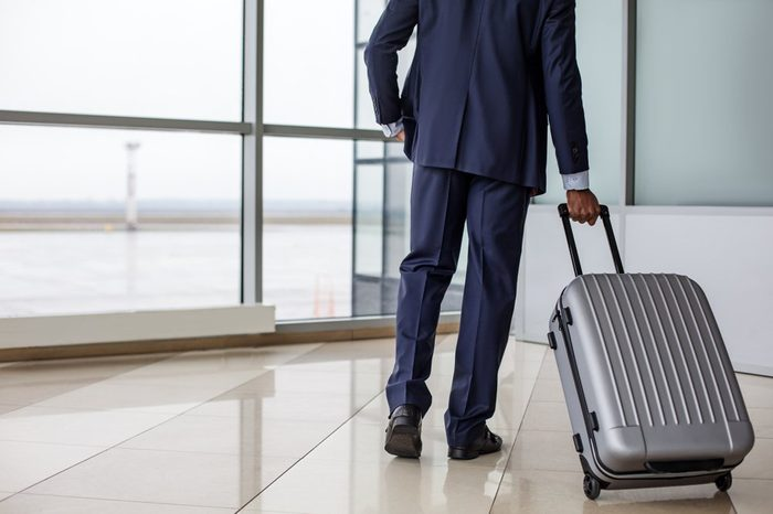 Travel concept. Back view of confident businessman in suit is walking along airport lounge while carrying his suitcase. Copy space in the left side