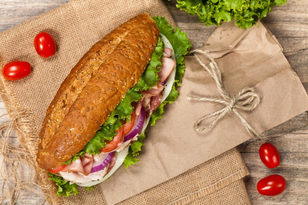 Nutritionists never order - Italian Sub Sandwich with Salami, Tomato, and Lettuce. Selective focus.