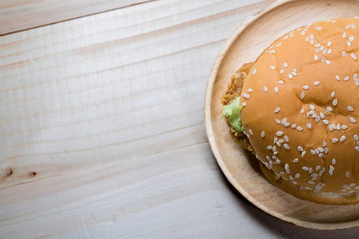 Sandwich with chicken burger on wooden plate. on top
