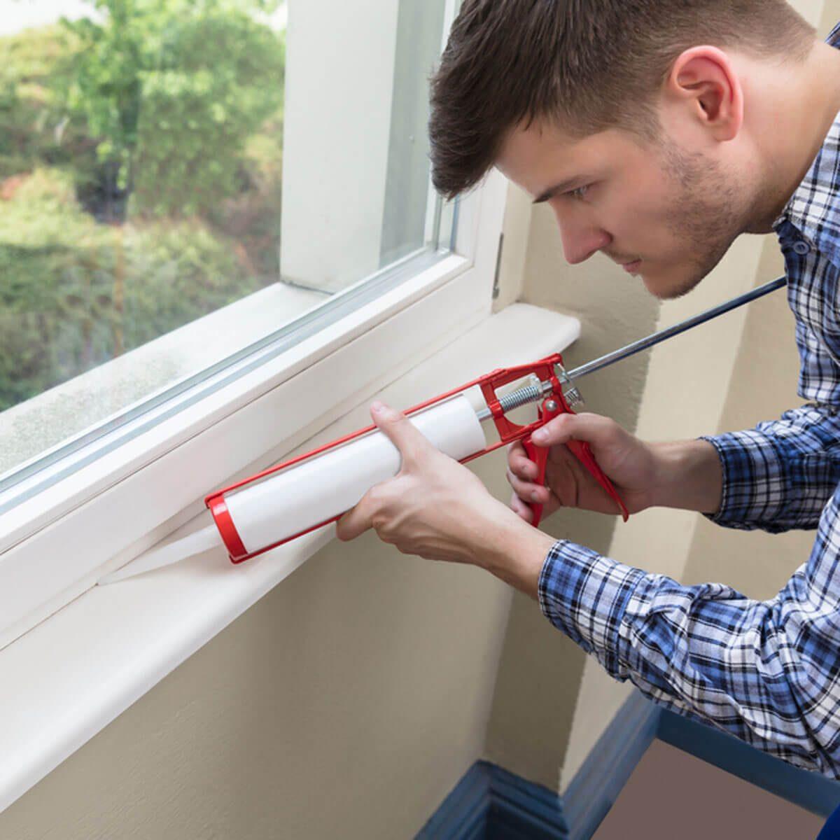 shutterstock_686328526 caulk a window to keep your home warm