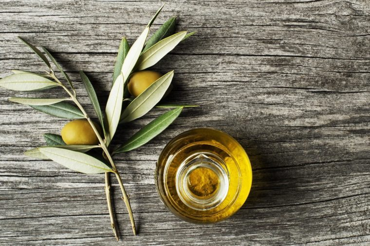 Olive oil and olive branch on wooden table