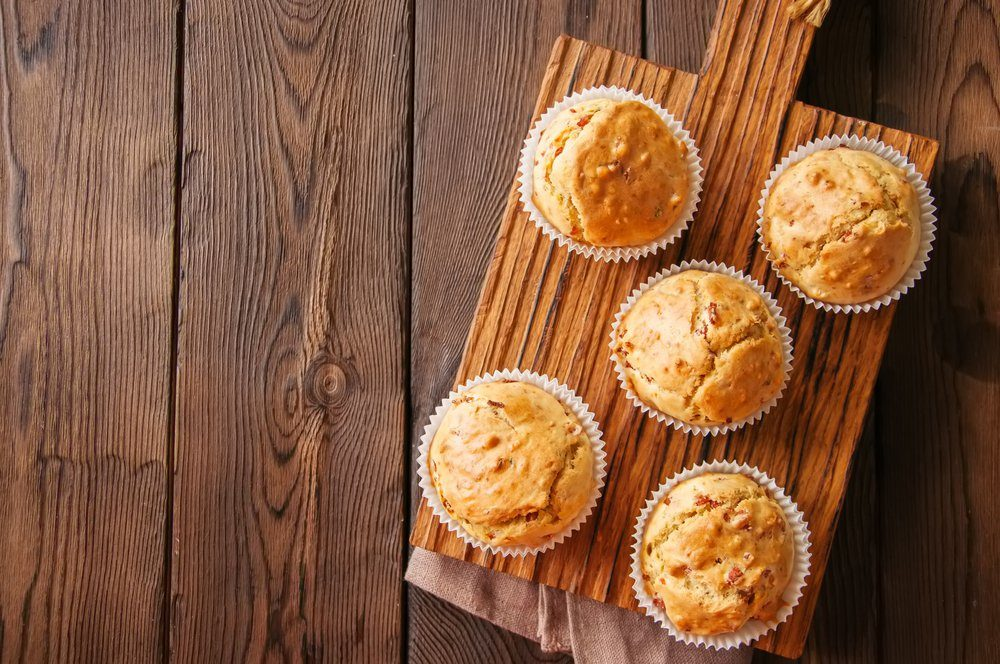 nutritionists never order - Homemade muffins with bacon and cheese on a wooden background. Healthy snack or breakfast meal.
