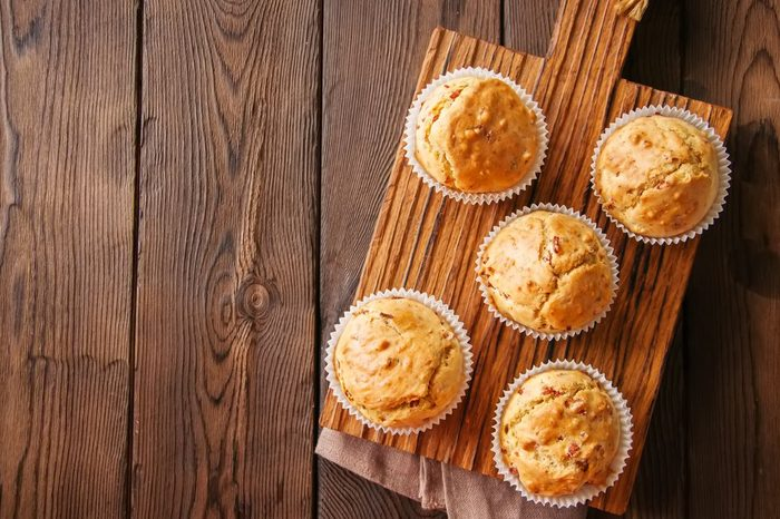 Homemade muffins with bacon and cheese on a wooden background. Healthy snack or breakfast meal.