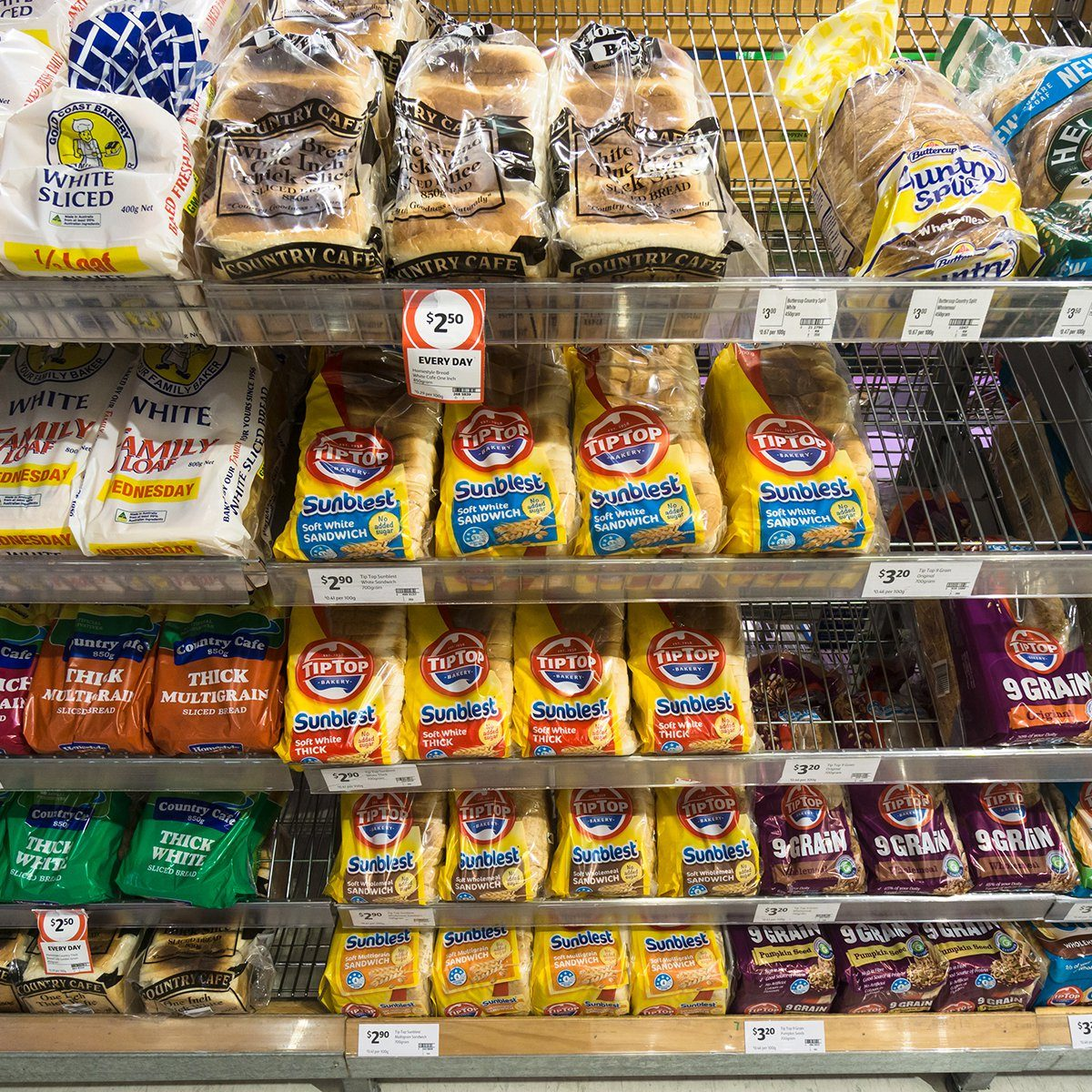 Sliced bread and toast from various brands such as tiptop and Multicafe are displayed in a supermarket.