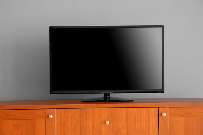 what do burglars want - wide screen TV on wooden commode near grey wall
