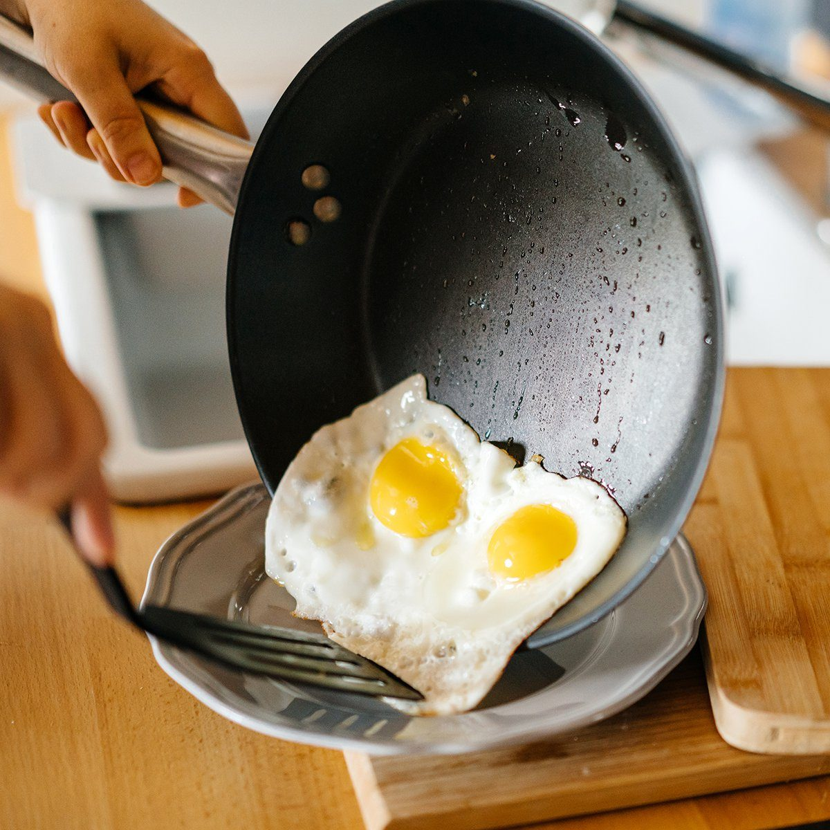 Two fried eggs in a pan with olive oil.