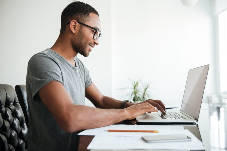 Happy african young man dressed in gey t-shirt and wearing eyeglasses using laptop and sitting at the table.