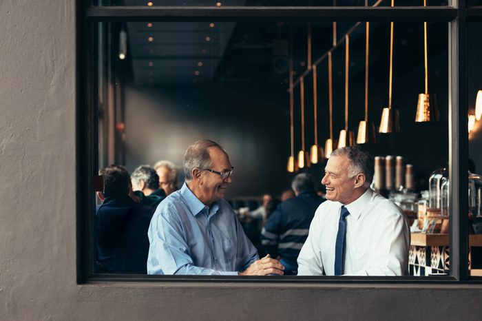 Two business partners having a casual discussion at cafe after work. Happy senior businessmen talking and smiling at a restaurant.