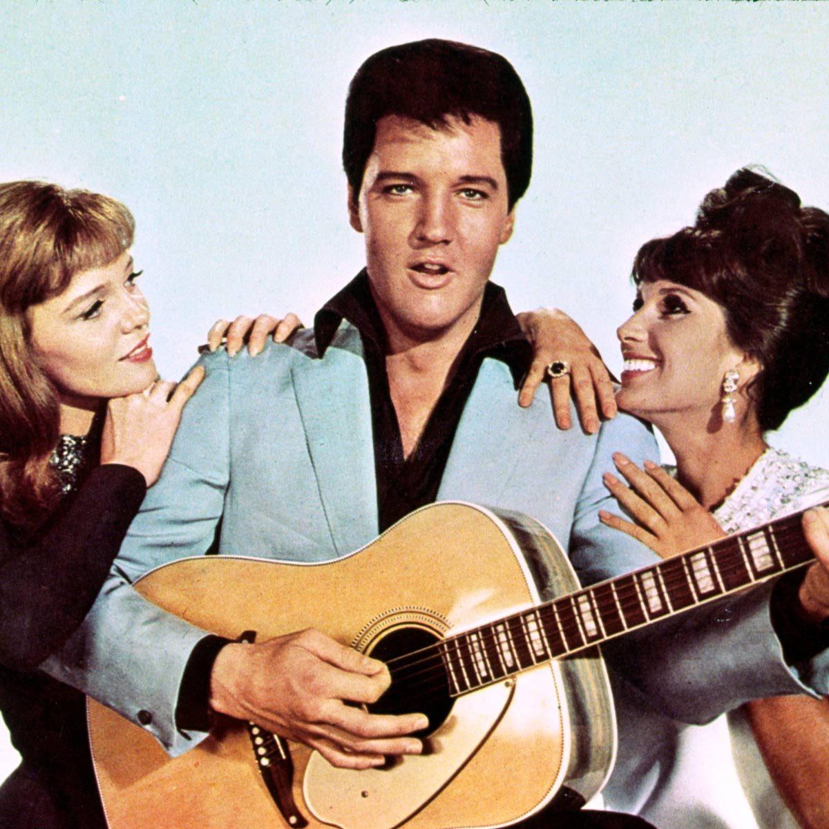 Elvis with guitar standing between two adoring women