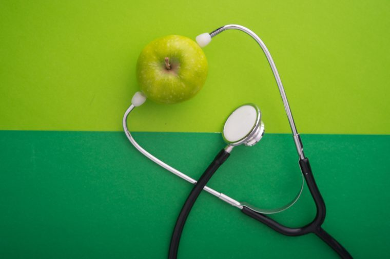A green apple with stethoscope on green color paper background