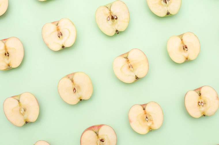 Background of cut in half apples on green background. Top view