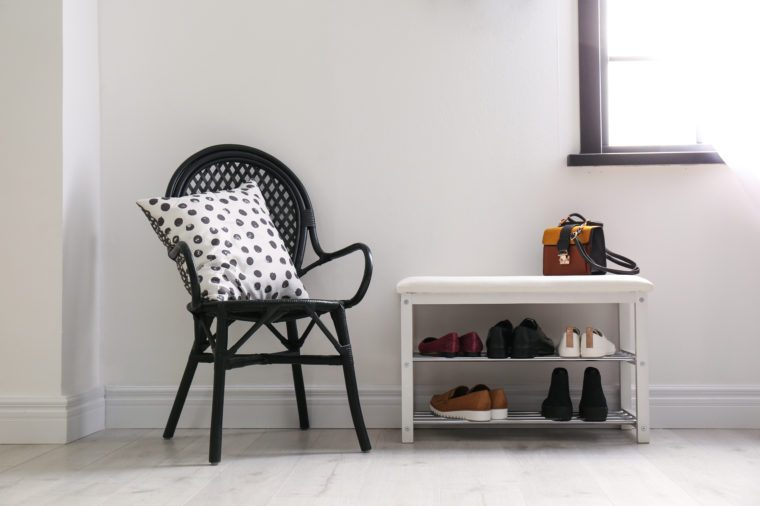 Collection of stylish shoes on rack storage near white wall in room