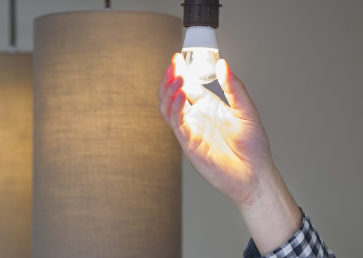 A man turning a lighted lightbulb in his own new house