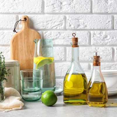 Fresh olive oil and kitchen utensils on table near brick wall