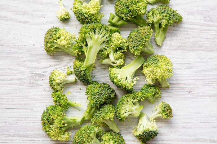 Freshly cut raw broccoli on white wooden surface, overhead view. Flat lay, from above.