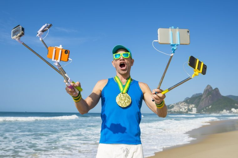 Gold medal athlete smiling for his many gadgets on selfie sticks as he poses for a picture on Ipanema Beach in Rio de Janeiro, Brazil