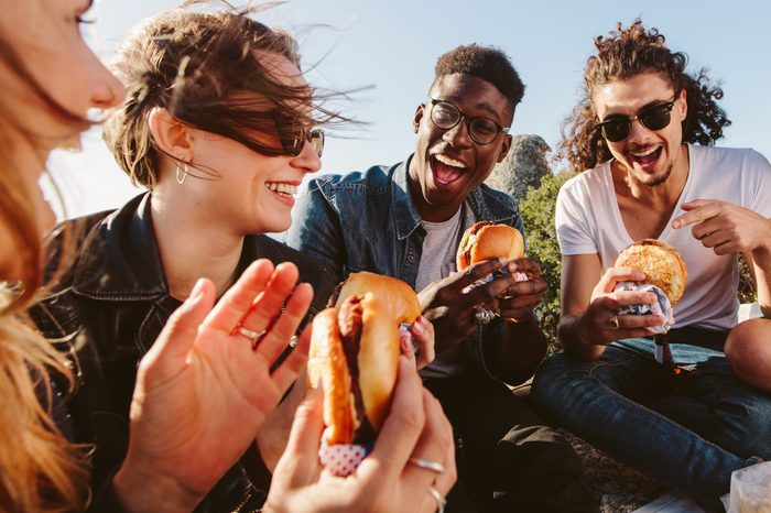 Group of friends sitting on mountain top eating burger. Excited young men and women enjoying and partying outdoors.