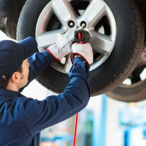 Mechanician-changing-car-wheel-in-auto-repair-shop