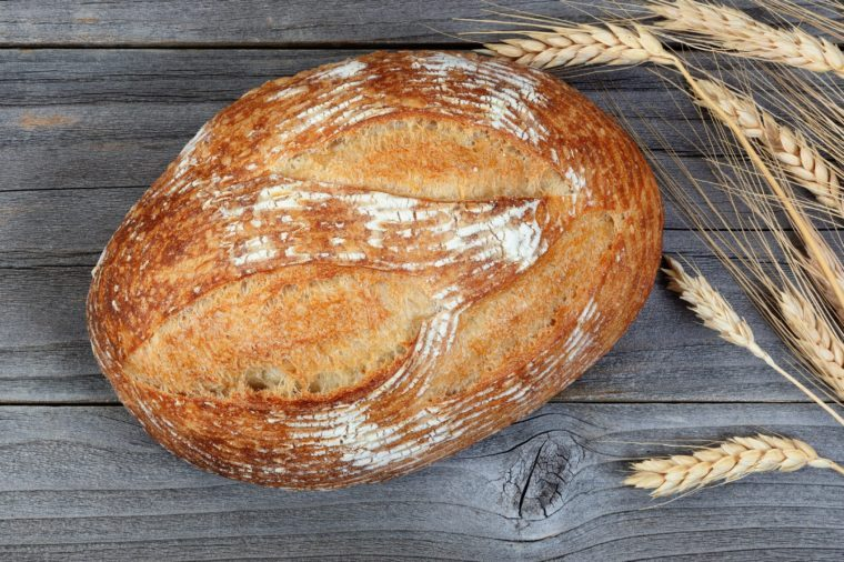 Overhead view of baked whole loaf of bread and wheat stalks on rustic wooden boards