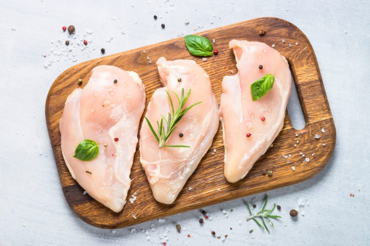 Raw chicken fillet with spices and herbs on cutting board. Light stone table top view.
