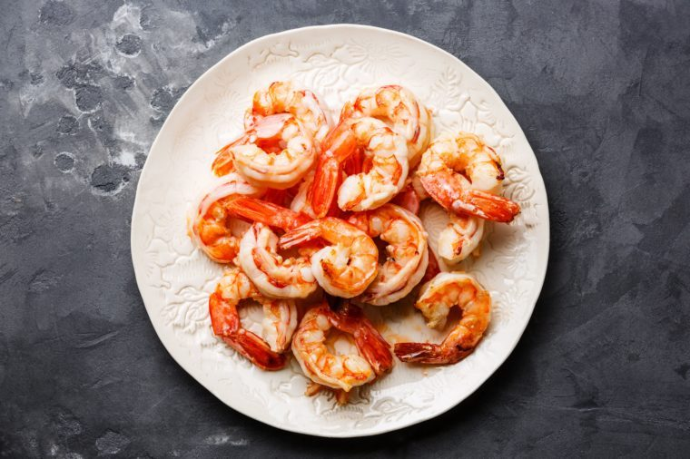 Roasted Prawns on white plate on gray concrete stone background