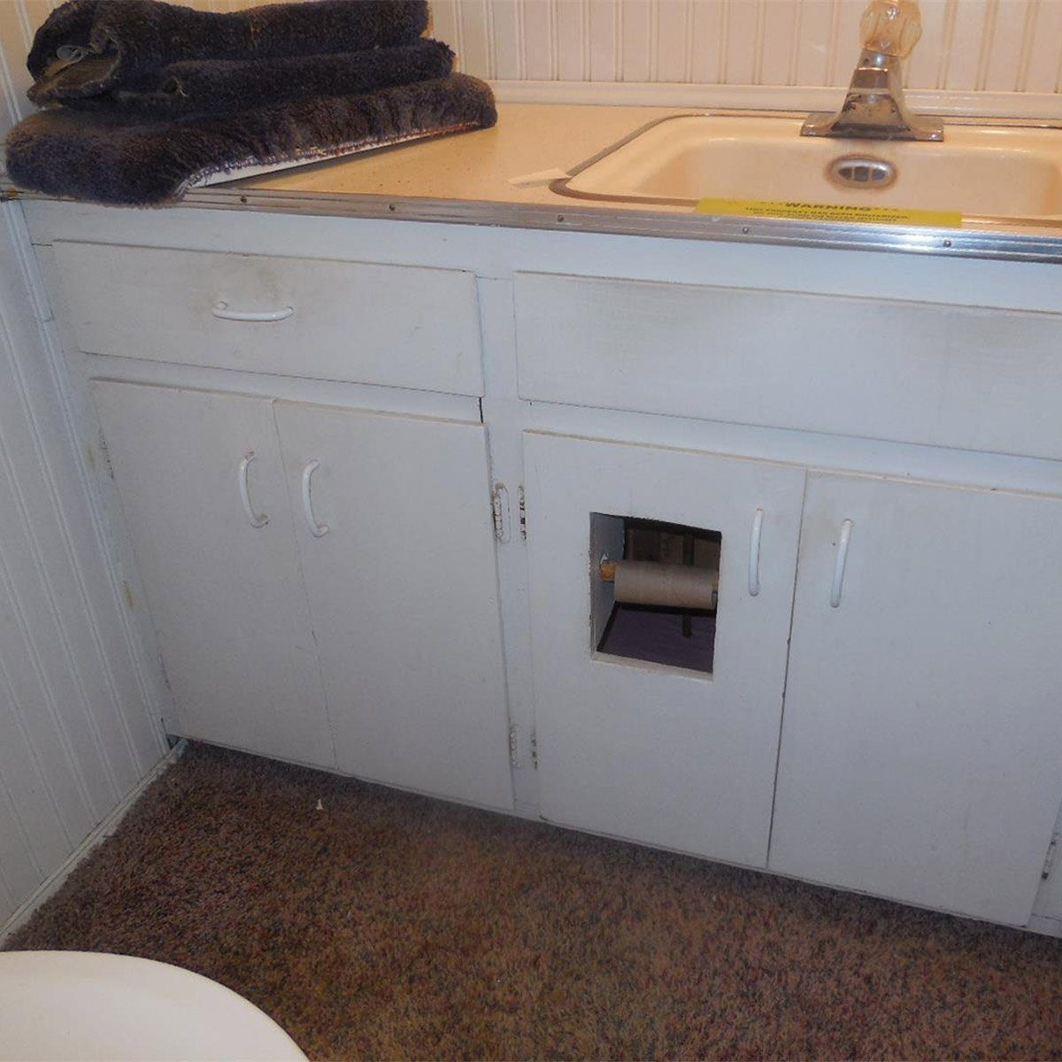 toilet paper holder in cabinet