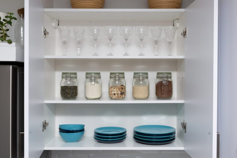 Various seeds in storage jars in pantry, white modern kitchen in background. Smart kitchen organization