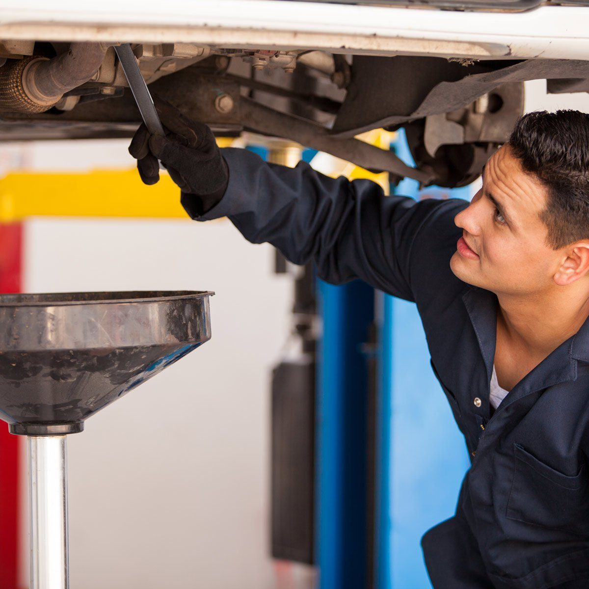 Young-Hispanic-mechanic-draining-engine-oil-from-a-car-for-an-oil-change-at-an-auto-shop
