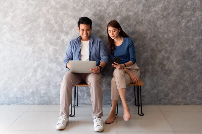Asian couple man and woman using laptop computer wall background with copy space