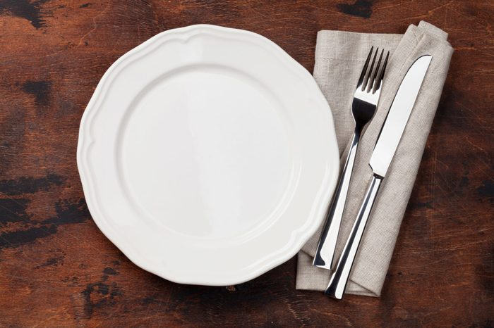 Table setting. Empty plate, knife, fork and napkin. Top view and flat lay with copy space