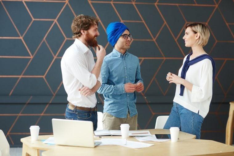 Intercultural men interviewing young female in studio