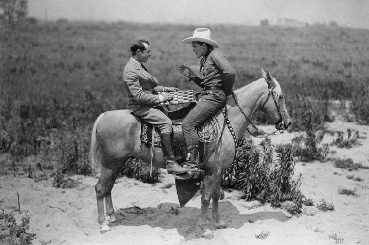 Cowboy and businessman playing checkers on horseback