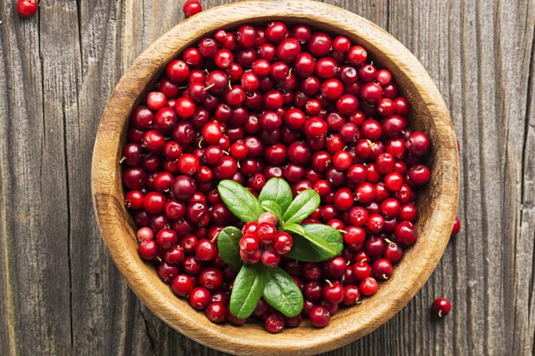 Ripe northern lingonberry in a wooden bowl on a background with twigs and leaves. Top View