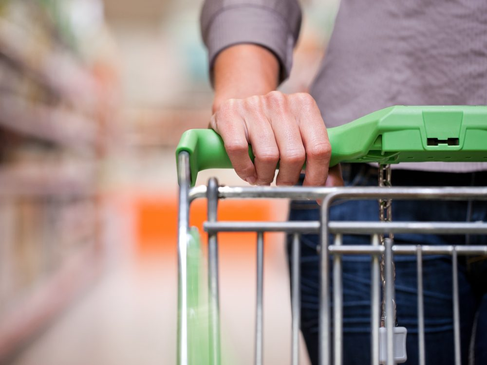 Woman pushing shopping cart at supermarket