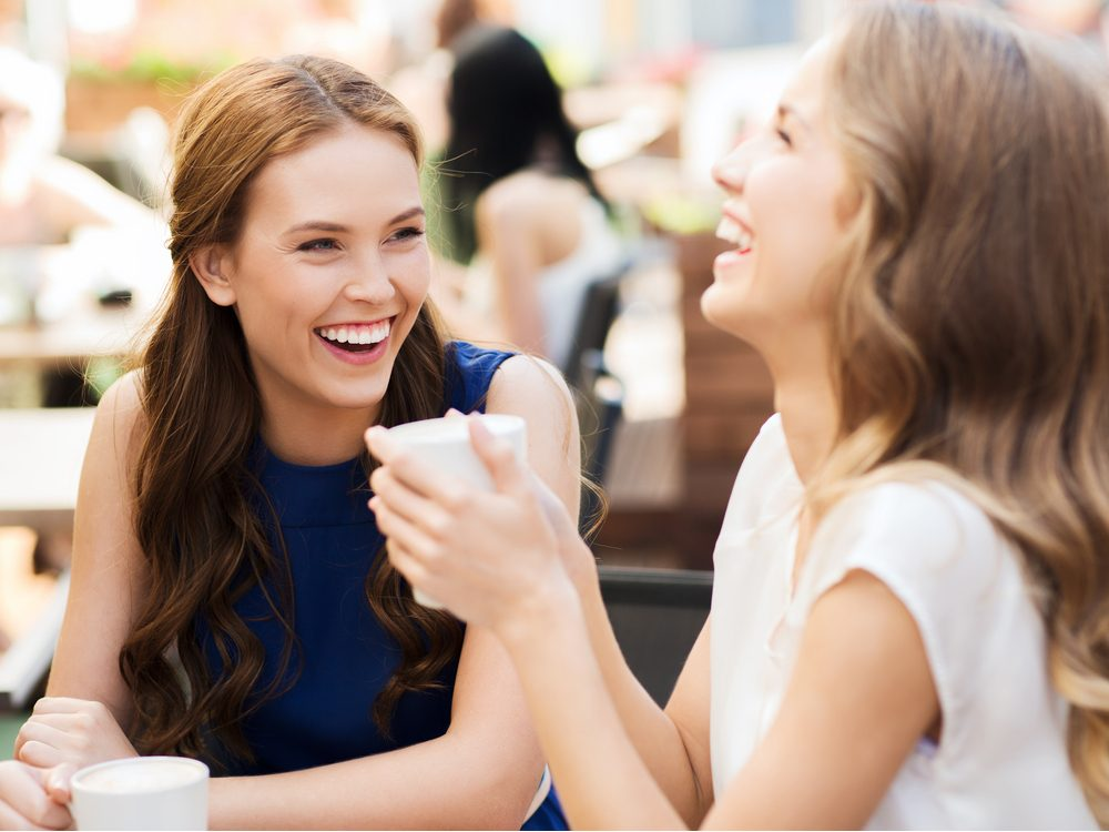 Two female friends talking over tea
