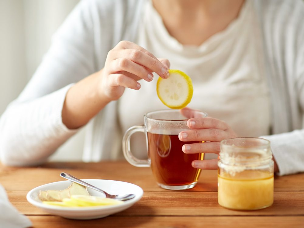 Dipping lemon slice into a cup of tea