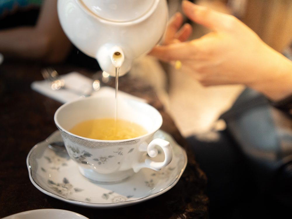 Pouring tea into teacup