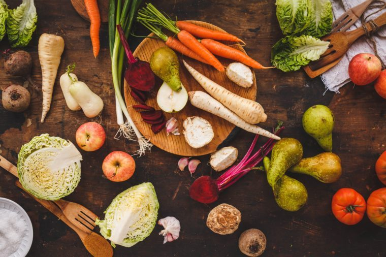 Autumn fruit and roots veggies background. Healthy, garden local produce. Rustic dark style. Horseradish, leeks, beetroot, parsley roots, celery plants, apple, pear.