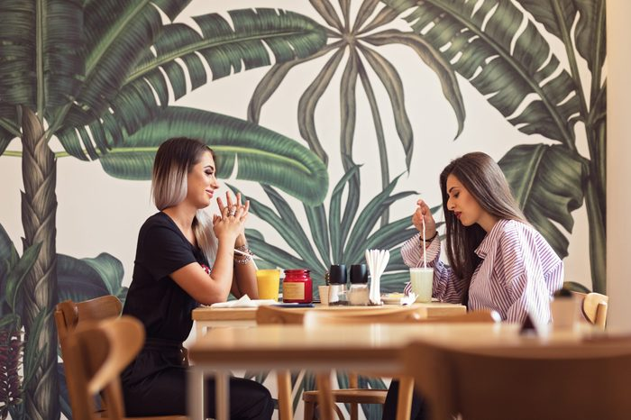 girlfriends out in town for drinks, lunch, spending quality time, eating tasty food and drinking together. Girls waiting for friend to make important announcement getting excited to hear new secret