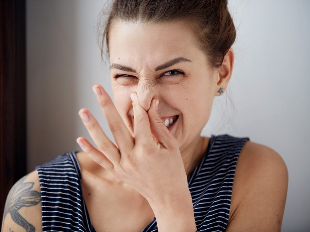 Woman covering nose from body odour