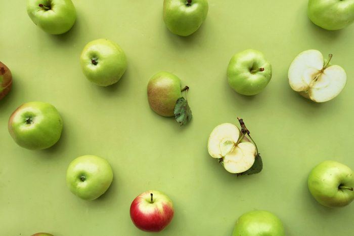 green apples on a green background flat layout top view. Fruits pattern.