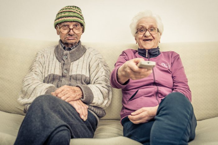 old couple watching television on the couch in the living room. concept about aging, old people, entertainment, humor and people