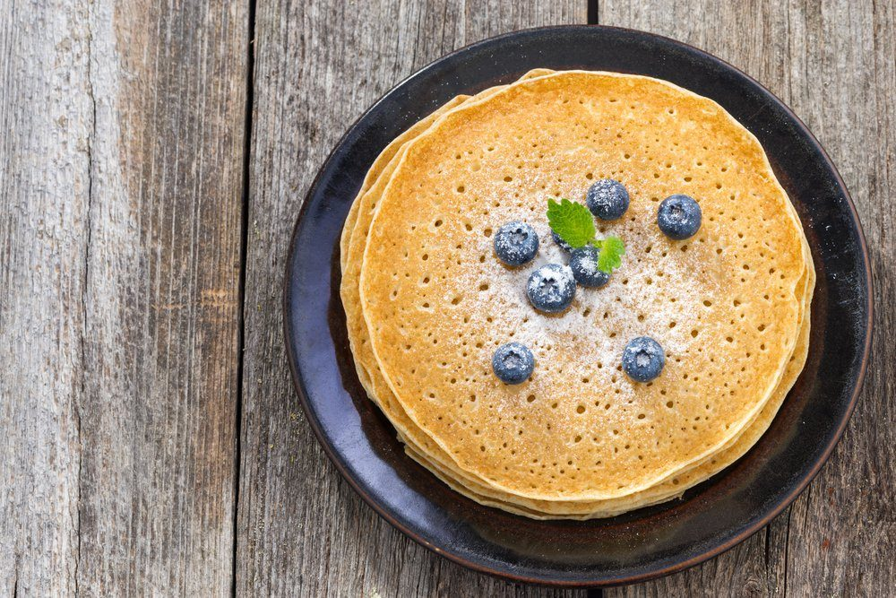 crepes with fresh blueberries on wooden table, top view, horizontal