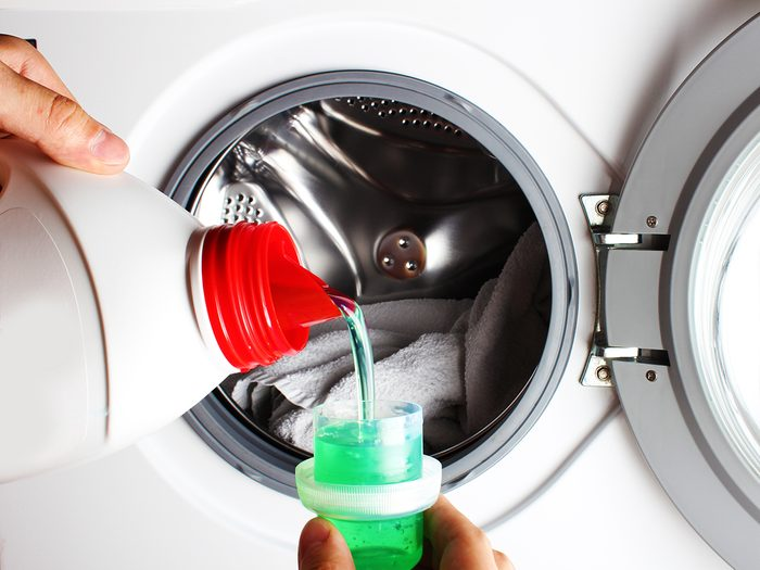 Pouring laundry detergent into washer
