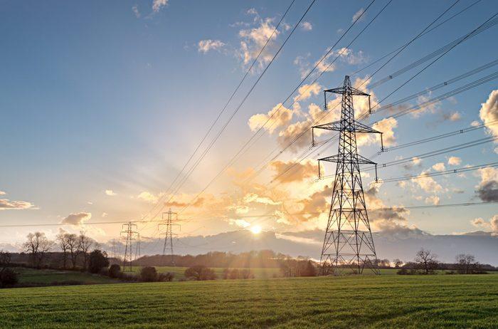 Electricity Pylon - UK standard overhead power line transmission tower at sunset.